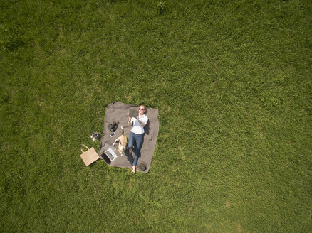 Bird's eye view of woman lying on blanket on meadow with dog using tablet - ONF01123