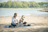 Woman sitting on blanket at a river with dog wearing headphones and using laptop - ONF01126
