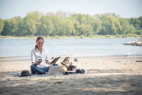 Woman sitting on blanket at a river with dog using portable devices - ONF01129