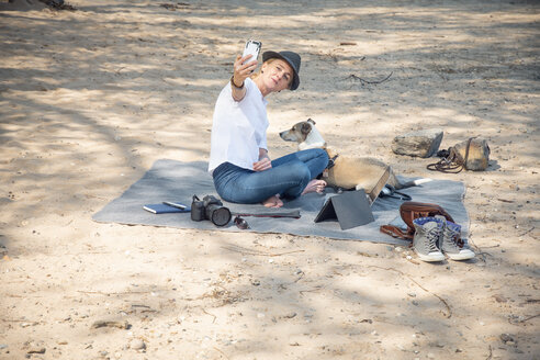Woman sitting on blanket on beach with dog taking a selfie - ONF01132