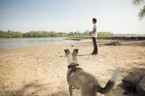 Man with a dog flying drone at a river - ONF01135