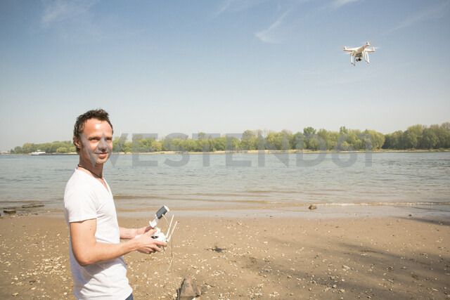 Portrait of smiling man flying drone at a river - ONF01144 - noonland/Westend61