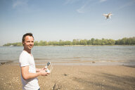 Portrait of smiling man flying drone at a river - ONF01144