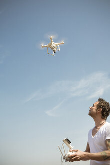 Man flying drone under blue sky - ONF01147