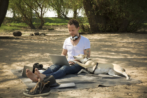 Man with dog sitting on blanket at a beach using laptop - ONF01150