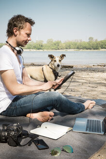 Man with dog sitting on blanket at a river using tablet - ONF01153