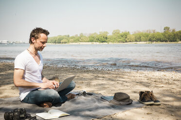 Man sitting on blanket at a river using laptop - ONF01156