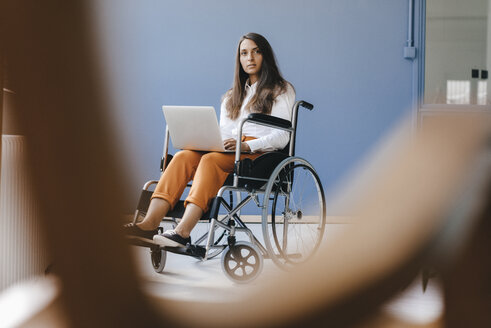 Young handicapped woman sitting in wheelchair, using laptop - KNSF03905