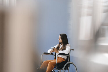 Young handicapped woman sitting in wheelchair, looking worried - KNSF03908
