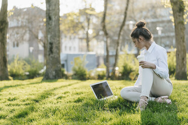 Young businesswoman taking break, using laptop, sitting in grass and drinking coffee - KNSF03926