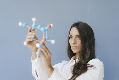Female scientist holding molecule model, looking for solutions - KNSF03935