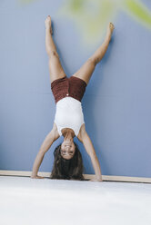 Young woman doing handstand against wall - KNSF03944