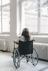 Young handicapped woman sitting in wheelchair, rear view - KNSF03947
