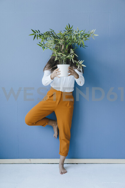Pretty young woman holding potted plant in front of her face - KNSF03956