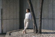 Young businesswoman leaning against atree in a backyard - KNSF03962