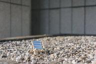 Empty deckchair on pebbles - KNSF03965