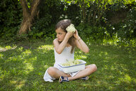 Little girl sitting on meadow in the garden with bowl of picked elderflowers - LVF07021