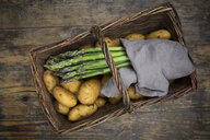 Organic green asparagus and organic potatoes in wickerbasket on wood - LVF07024