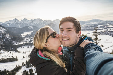 Hiking couple taking selfie overlooking snow covered Allgau Alps, Bavaria, Germany - CUF22848