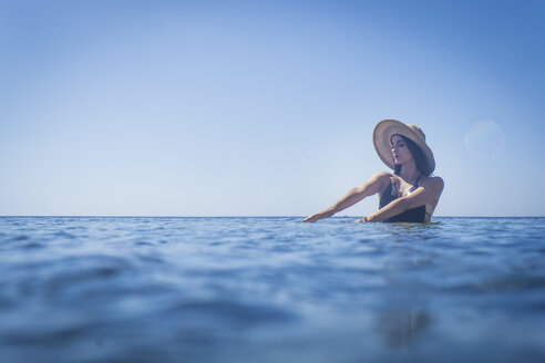 Young woman wearing sunhat wading in deep blue sea, Villasimius, Sardinia, Italy - CUF22959