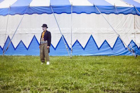 Portrait of senior male circus clown outside circus tent - CUF22980