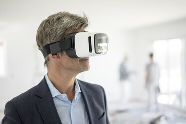 Man in suit wearing VR glasses in building under construction - MOEF01238