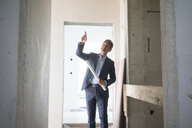 Architect with blueprint pointing his finger in building under construction - MOEF01244