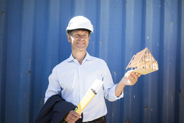 Smiling architect wearing hard hat holding house model - MOEF01247