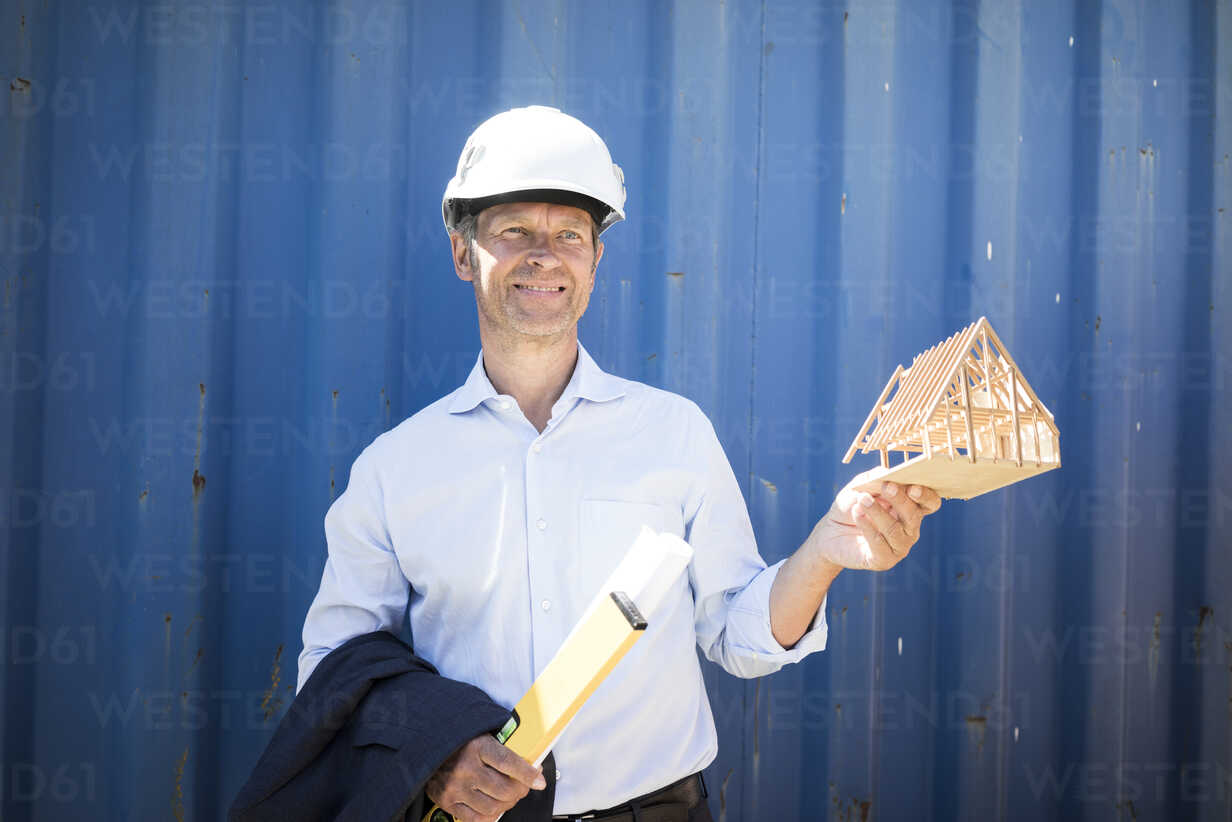 Smiling architect wearing hard hat holding house model - MOEF01247 - Robijn Page/Westend61