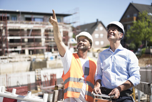 Smiling construction worker talking to man on construction site - MOEF01259