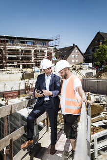 Man in suit with tablet talking to construction worker on construction site - MOEF01265