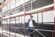 Architect wearing hard hat standing on scaffolding on construction site - MOEF01292