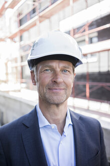 Portrait of confident architect wearing hard hat on construction site - MOEF01295