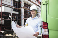 Portrait of architect with blueprint wearing hard hat on construction site - MOEF01298