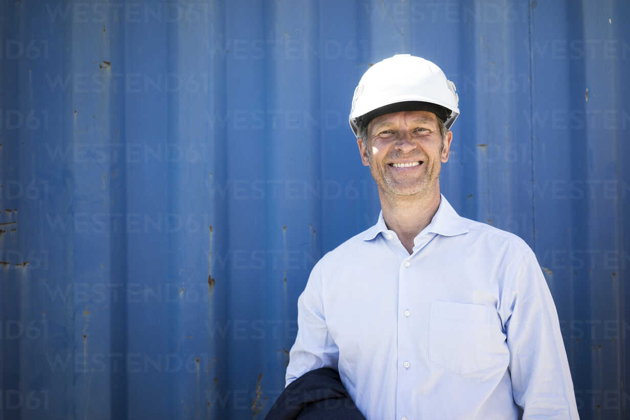 Portrait of smiling man wearing shirt and hard hat - MOEF01301 - Robijn Page/Westend61