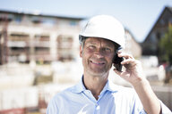 Portrait of smiling man wearing hard hat on cell phone on construction site - MOEF01307