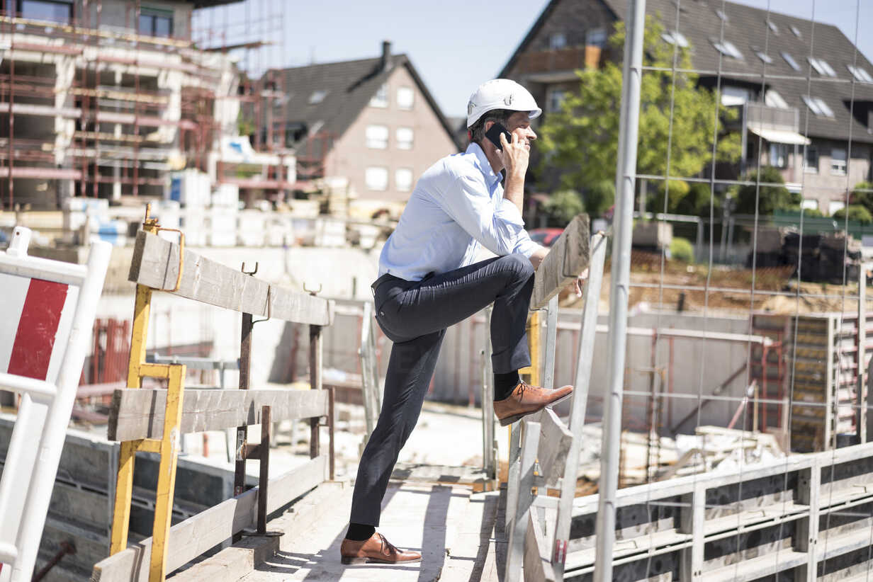 Man wearing hard hat on cell phone on construction site - MOEF01316 - Robijn Page/Westend61