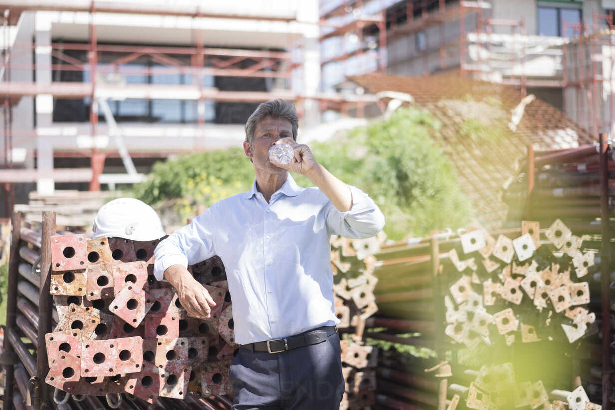 Man on construction site drinking water from bottle - MOEF01319 - Robijn Page/Westend61