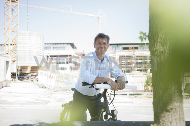 Portrait of man with e-bike on construction site - MOEF01322 - Robijn Page/Westend61