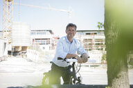 Portrait of man with e-bike on construction site - MOEF01322