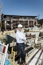 Portrait of smiling man wearing hard hat on construction site - MOEF01325