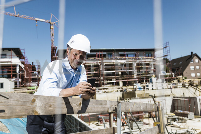 Man wearing hard hat using cell phone on construction site - MOEF01328 - Robijn Page/Westend61