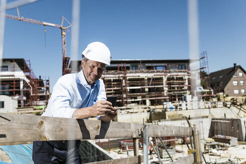 Man wearing hard hat using cell phone on construction site - MOEF01328