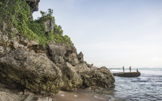 Three men on coastal rock at Panawa Beach, Bali, Indonesia - CUF23009