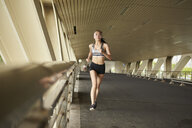 Woman jogging on elevated walkway - CUF23048