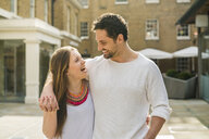 Young couple laughing on Kings Road, London, UK - CUF23072