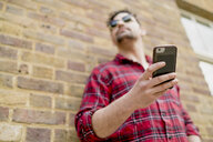 Low angle view of young man leaning against brick wall holding smartphone - CUF23075