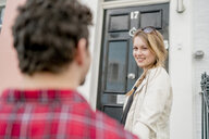Young woman and boyfriend at front door, Kings Road, London, UK - CUF23078