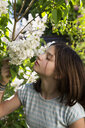 Portrait of girl smelling blossom of white lilac - LVF07033