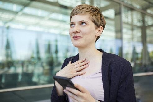 Portrait of blond businesswoman using smartphone - PNEF00682